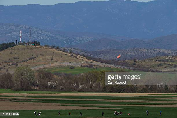 The Macedonian flag flies above the border fence between Greece and Macedonia as refugee families walk through fields towards a refugee camp on March...