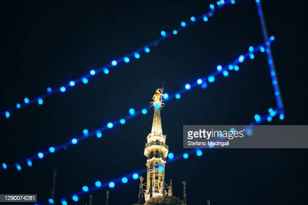 the madonnina del duomo in milan illuminated at night among the blue christmas lights, seen from below - sistine madonna stock pictures, royalty-free photos & images
