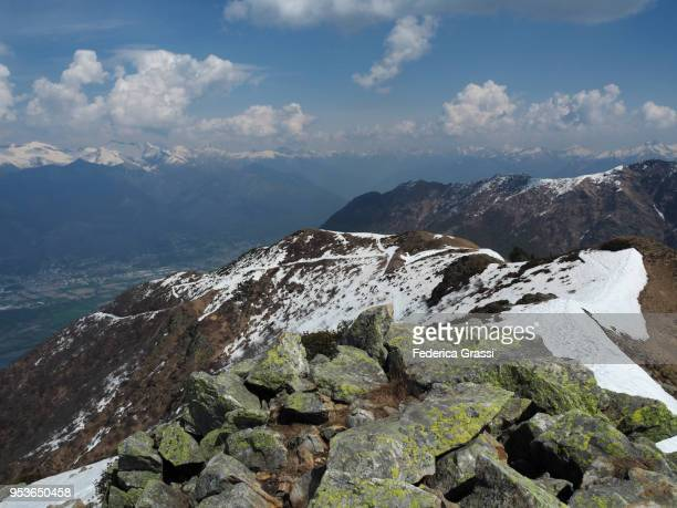 The Maggia river delta with the cities of Locarno and Ascona seen from the top of Mount Gambarogno on a sunny April afternoon. Situated in Canton of Ticino, Southern Switzerland. The Swiss Alps are visible in the background, still covered with snow in lat