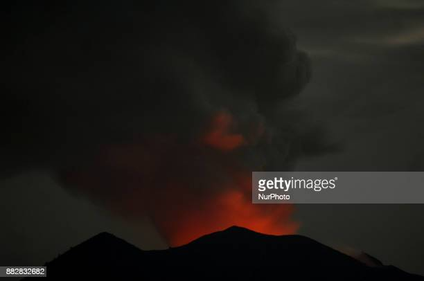 The magma light in the crater of Mount Agung reflected off the visible volcanic ash Karangasem Bali Indonesia on November2017 Smoke to earthquake...
