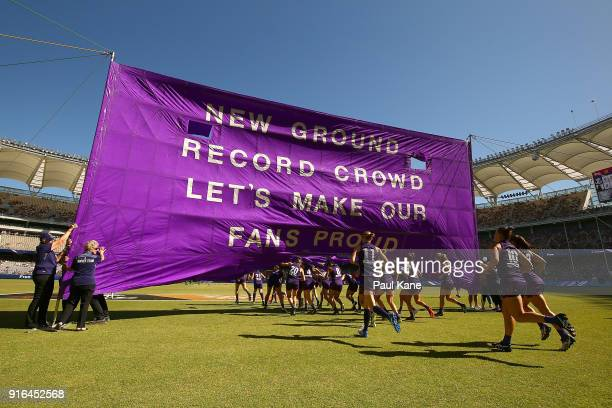 The Magpies run onto the field during the round two AFLW match between the Fremantle Dockers and the Collingwood Magpies at Optus Stadium on February...