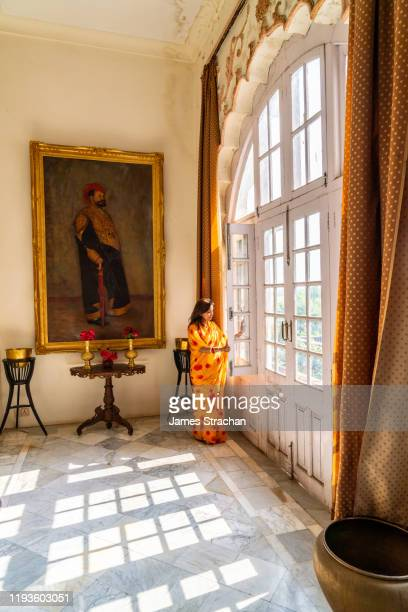 the maharani (maharajah's wife) of jhalawar opening a window and looking down on the garden at her home, the former hunting lodge of the maharajas of jhalawar, now run by the family as prithvi vilas palace hotel, jhalawar, rajasthan, india (model and prop - james strachan stock pictures, royalty-free photos & images