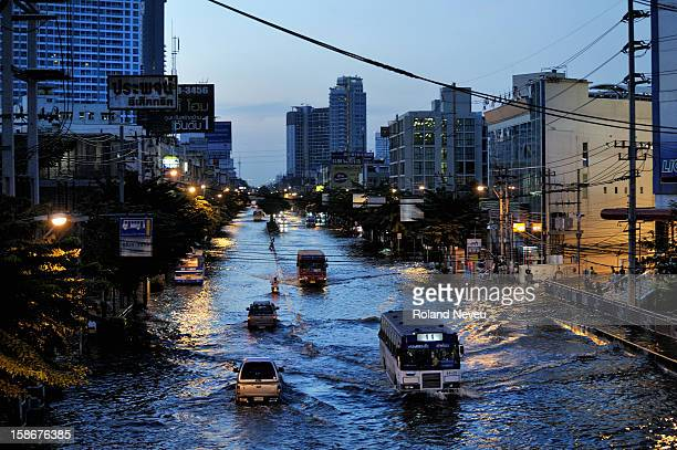 The main avenue of northern Bangkok are transformed as rivers Traffic is made of trucks somes buses and boats As night fall on Payonyothine avenue