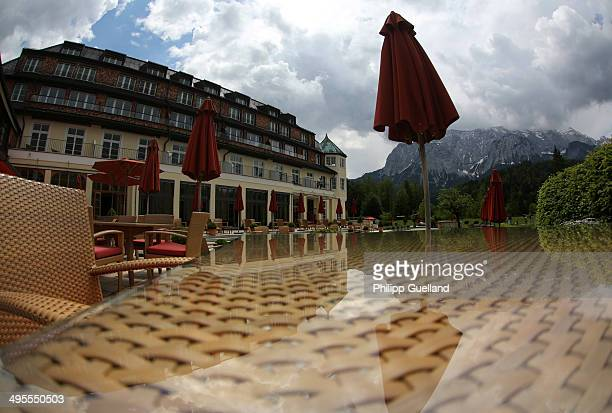 The main building and the surrounding Wetterstein mountains are reflected in a table on the hotel terrace at Schloss Elmau, a luxury spa hotel, in...