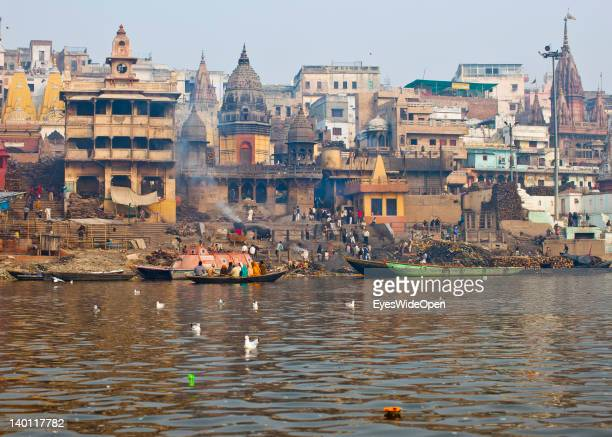 The main burning Ghat Manikarnika where dead Hindu bodies are cremated on funeral piles and boats are delivering wooden piles seen from the Ganges...