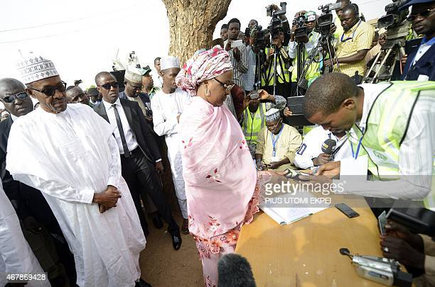 The main opposition All Progressives Congress presidential candidate Mohammadu Buhari watches his wife Aisha register to vote on March 28 2015 in...