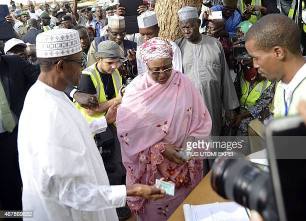 The main opposition All Progressives Congress presidential candidate Mohammadu Buhari holds his voter's card to register with his wife Aisha on March...