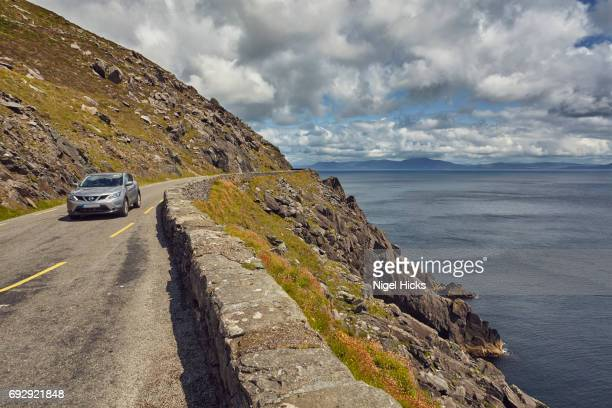 The main road snaking along vertical cliffs at Dunmore Head, at the western end of the Dingle Peninsula, County Kerry, Ireland.