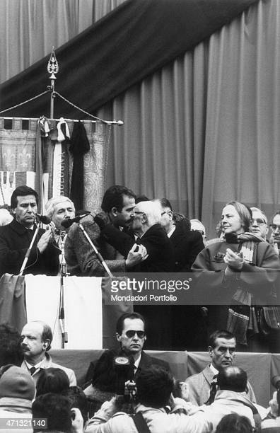 The maior of Bologna Renzo Imbeni and the President of the Italian Republic Sandro Pertini hugging each other watched by the President of the Chamber...