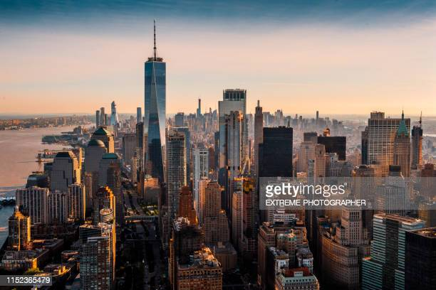 the majesty of manhattan island taken from a helicopter above the downtown area at a golden hour - new york city stock pictures, royalty-free photos & images