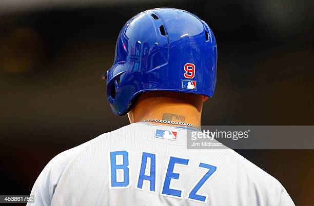 The Major League Baseball logo is seen as a tattoo on the neck of Javier Baez of the Chicago Cubs during a game against the New York Mets at Citi...