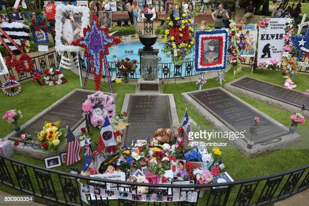 The maker is pictured in the Meditation Garden where Elvis Presley is buried alongside his grandmother and parents at his Graceland mansion on August...