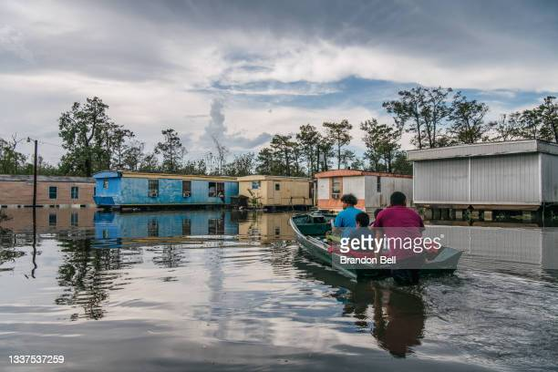 """The Maldonado family travel by boat to their home after it flooded during Hurricane Ida on August 31, 2021 in Barataria, Louisiana. """"I've lost..."""