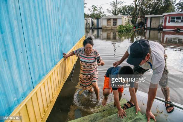 The Maldonado family walk up the steps to their trailer home after it was flooded during Hurricane Ida on August 31, 2021 in Barataria, Louisiana....
