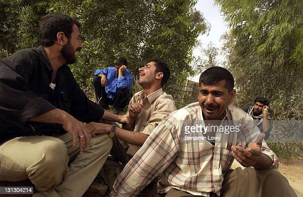The male members of the Al Musawi family openly weep following the exumation of Sayid Abdel Sattar from a numbered grave in a cemetery for Saddam...