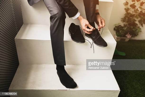 the man, a businessman, an entrepreneur or the groom sits on a white ladder and a new tying shoelace black suede shoes business, close-up. the concept of business, entrepreneurship, fashion. - suede shoe stock pictures, royalty-free photos & images
