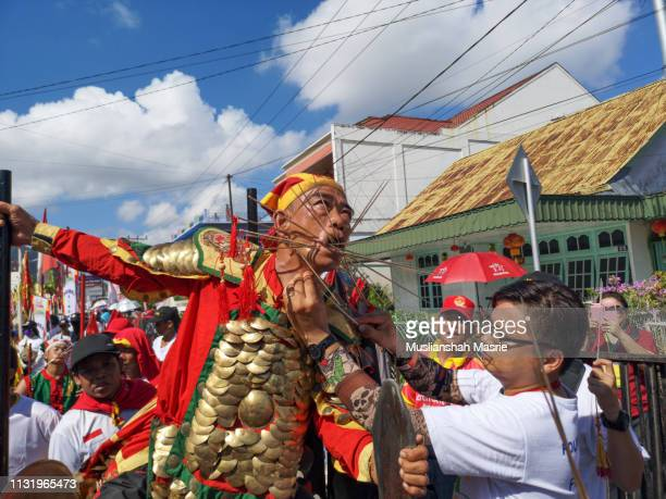 the man acting as ancient tatung torturing himself during chap go meh or cap goh meh festival 2019 in singkawang, west kalimantan, indonesia, borneo. - {{asset.href}} stockfoto's en -beelden