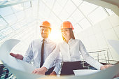The man and woman in a helmets hold the project plan in the building