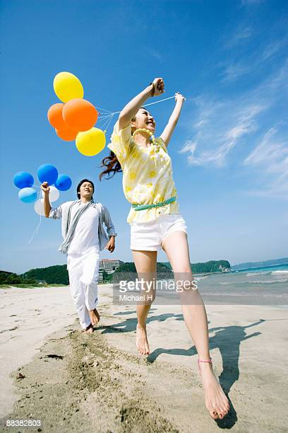 The man and woman who has the balloon is running i