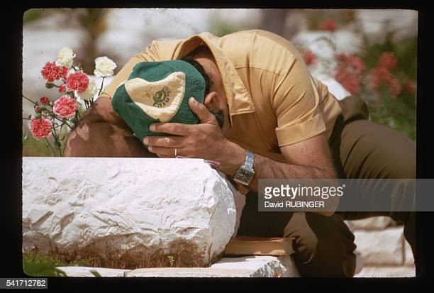 The man holds his head in grief at a Jewish military cemetery after the conclusion of the Yom Kippur War
