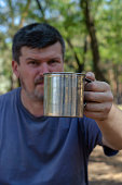 man holds out metal mug with