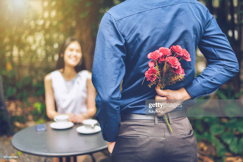 The man is hiding red flowers behind him in order to surprise his girlfriend. : Stock Photo