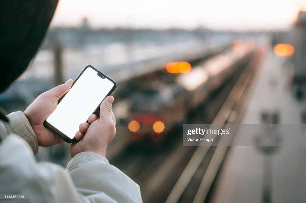 The Man is holding a mock up smartphone in his hand, against the background of the train at the railway station. : Stock Photo