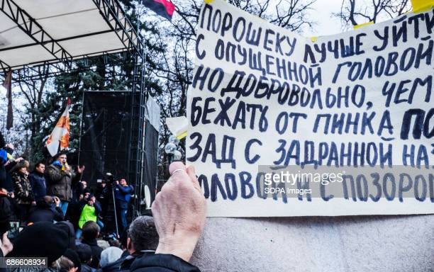 The man is holding a poster with the demand for the resignation of President Petro Poroshenko in front of the stage where Mikhail Saakashvili is...