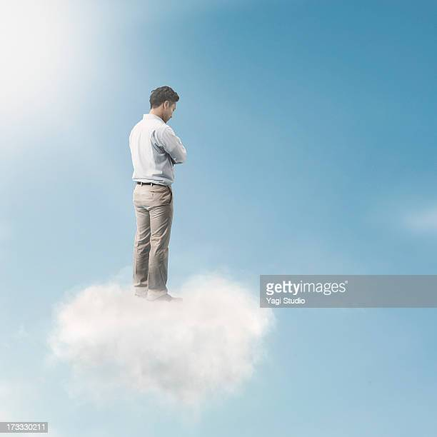 The man is looking down from above the clouds