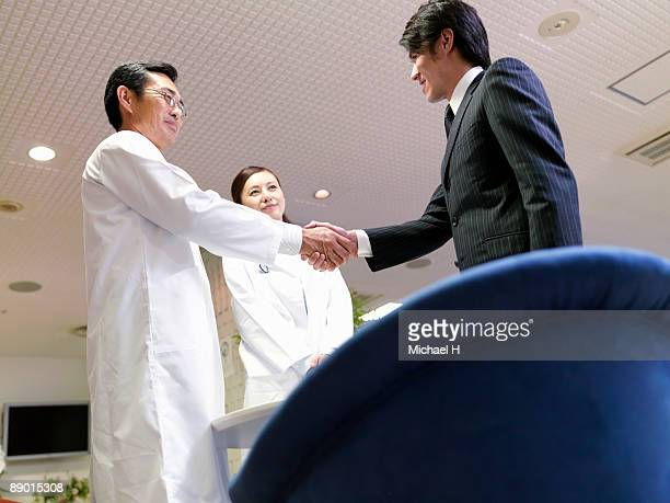 The man is shaking hands with the doctor.