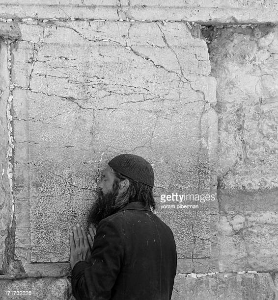 CONTENT] The man is standing very close to the wall whispering in great devotion BW portrait