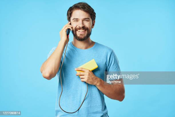 the man is talking on the smartphone and is charging the smartphone at the same time using the power bank. - low stock pictures, royalty-free photos & images