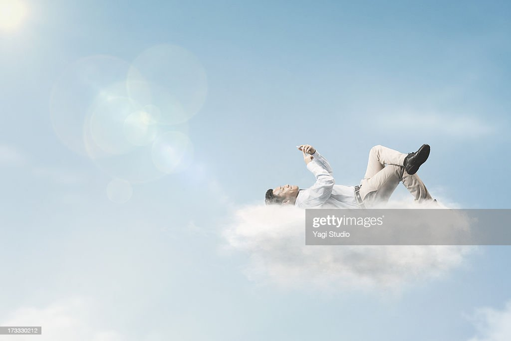 The man is using a smartphone above the clouds : Stock Photo