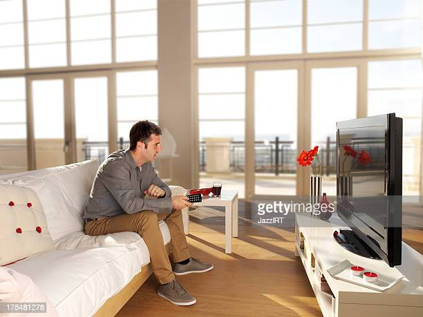 The man is watching tv in a living room