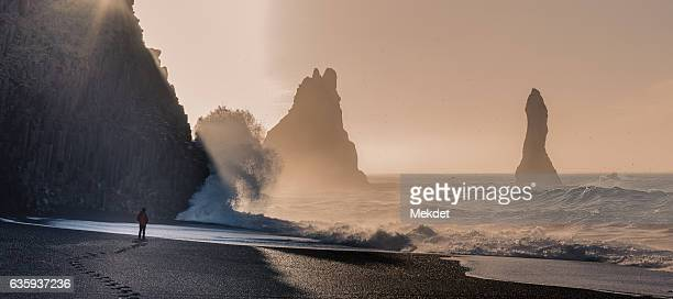 The man looking at the strong big wave hitting the Basalt column cliff at Reynisfjara, the Black Sand Beach, Iceland