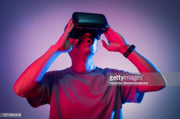 the man playing vr goggle with colorful lighting - cyberspace stock pictures, royalty-free photos & images
