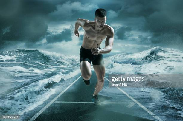 The man running and training on running track near the ocean waves