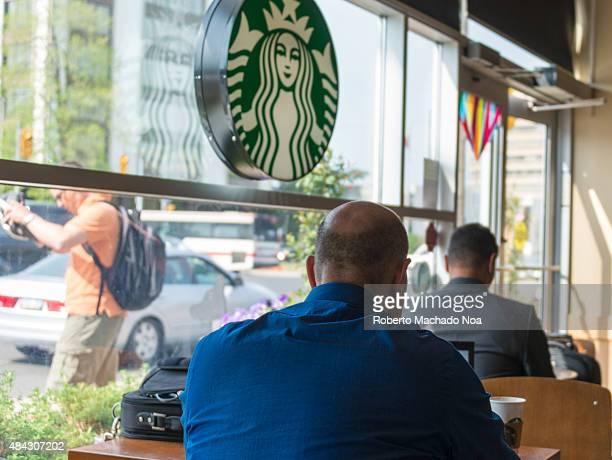 The man sitting in the cafeteria at the table near the window with the emblem Starbucks Starbucks Corporation doing business as Starbucks Coffee is...