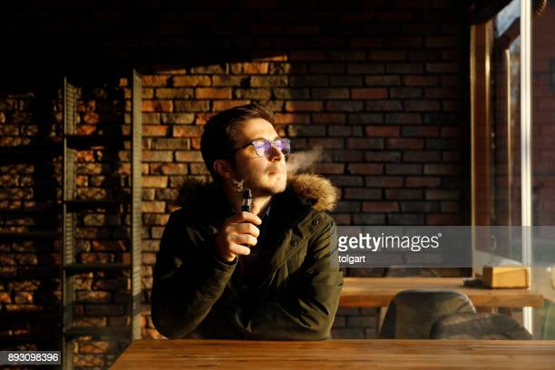 The man smoke an electronic cigarette at the cafe