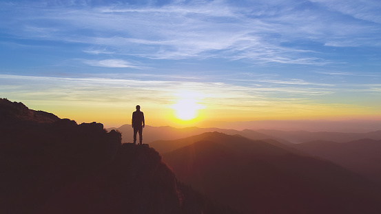 The man standing on the mountain on the picturesque sunrise background 1148587647
