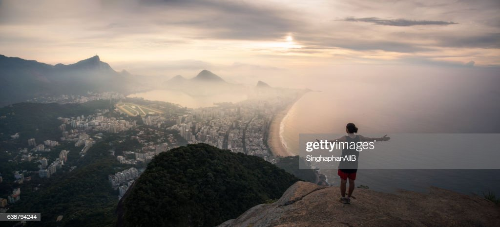 the man standing on the top of the Pedra da Gávea facing the top view of rio de janeiro, Brazil : Stock Photo