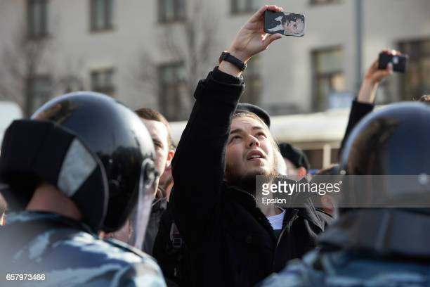The man takes a picture by the mobile phone with Lenin's image during an unauthorized anticorruption rally in Pushkin Square on Tverskaya Street on...