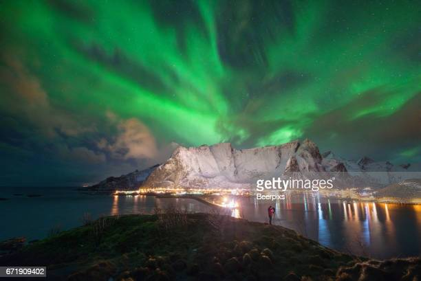The man was taking a picture with beautiful dancing aurora borealis over Hamnoy and Reine, Lofoten, Norway
