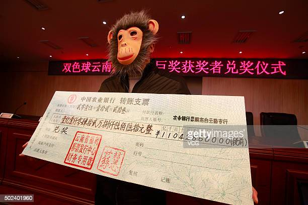 The man wearing a monkey mask poses with a cheque of over 110 million RMB lottery winnings at Yunnan welfare lotteries distribution center on...