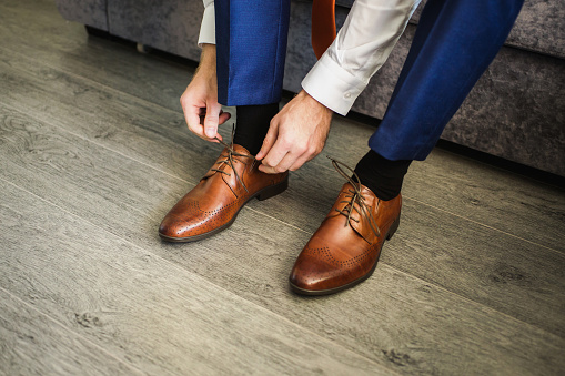 The man wears shoes. Tie the laces on the shoes. Men's style. Professions. To prepare for work, to the meeting. 685168074