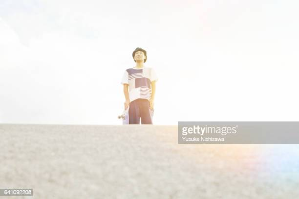 the man who stares at the distance with skateboarding - yusuke nishizawa stock pictures, royalty-free photos & images