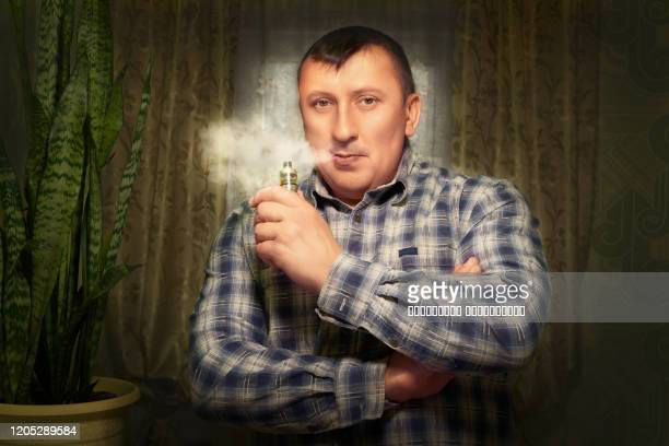 the man with an electronic cigarette. puffs of vapor from the vape. replacement of usual cigarettes. - hitech mod a stock pictures, royalty-free photos & images