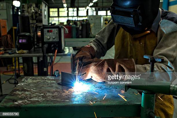 The man worker welding with sparks