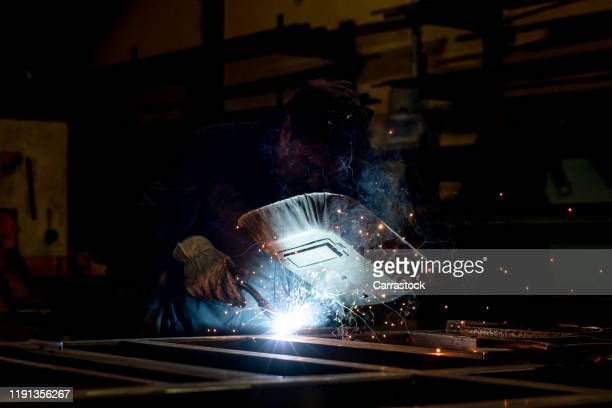 the man works by welding metal. - fabricage apparatuur stock pictures, royalty-free photos & images