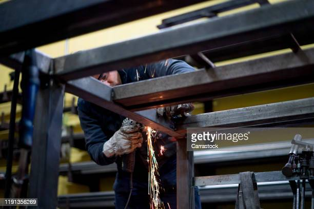 the man works with the machine grinder in locksmith. - fabricage apparatuur stock pictures, royalty-free photos & images